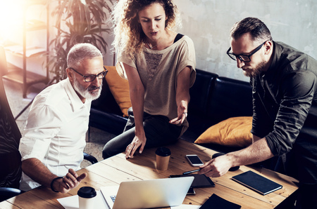 Young team of successful businessman found a great creative solution in modern coworking studio.Bearded man talking with colleagues about startup project.Business people brainstorm concept.Horizontal Standard-Bild