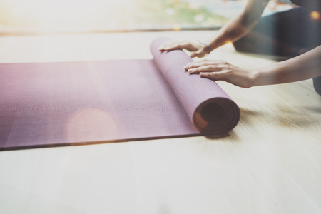 Closeup view of gorgeous young woman practicing yoga indoor. Beautiful girl preparing mats for practice class.Calmness and relax, female happiness concept.Horizontal, blurred background,flares