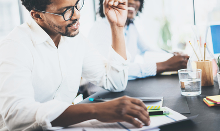 jovenes emprendedores: compañero de trabajo africano negro explaning tarea de negocios en el cumplimiento de room.Two jóvenes empresarios que trabajan juntos en un office.Horizontal moderna, fondo borroso