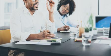 jovenes empresarios: Hombre de negocios negro africano explaning estrategia de negocios en el cumplimiento de room.Two empresarios jóvenes que trabajan juntos en una amplia office.Horizontal moderna, fondo borroso