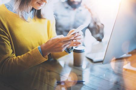 Jeune équipe de collègues qui travaillent ensemble dans coworking moderne space.Woman envoyer un message avec smartphone. Man travail sur le bureau computer.Horizontal, l'effet flare. arrière-plan flou