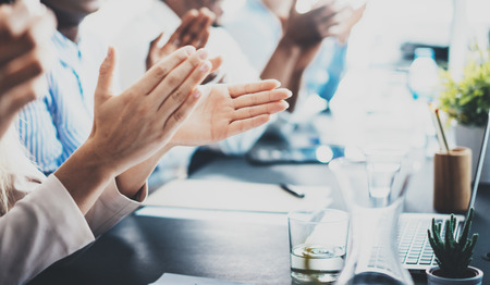 manos aplaudiendo: Closeup photo of partners clapping hands after business seminar. Professional education, work meeting, presentation or coaching concept.Horizontal,blurred background Foto de archivo