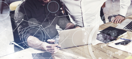 Concept of digital screen,virtual connection icon,diagram, graph interfaces.Two mans using together laptop,working in new startup project.Business people teamwork process.Wide,film effect,blurred 写真素材