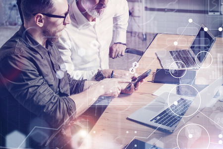 Concept of digital screen,virtual connection icon,diagram, graph interfaces.Adult businessman working together with young partner at the wooden table in modern office.Flares,blurred Banque d'images
