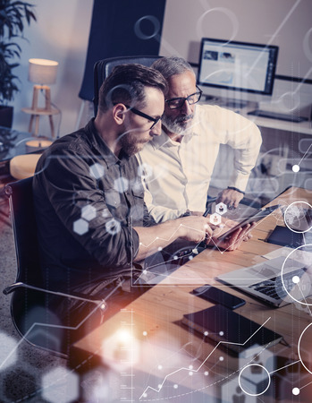 Concept of digital screen,virtual connection icon,diagram, graph interfaces.Adult businessman working together with young partner in modern office.Using mobile gadgets.Flares,blurred,vertical Reklamní fotografie