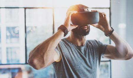 Attractive bearded man enjoyingvirtual reality glasses in modern interior design coworking studio.Home play concept.Smartphone use with VR goggles headset. Horizontal,flare effect,blurred background