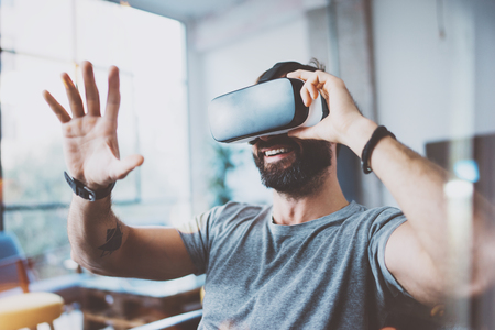 현대적인 인테리어 디자인 동역 스튜디오에서 가상 현실 안경을 착용하는 젊은 수염 남자. 스마트 폰 VR 고글 헤드셋 사용. 수평, 플레어 효과, 배경을