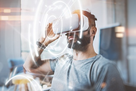 Concept of digital screen,connection and interfaces.Young beraded hipster enjoyingvirtual reality glasses in modern design loft studio.Smartphone use with VR goggles headset.Sunny,flare effect,blurred
