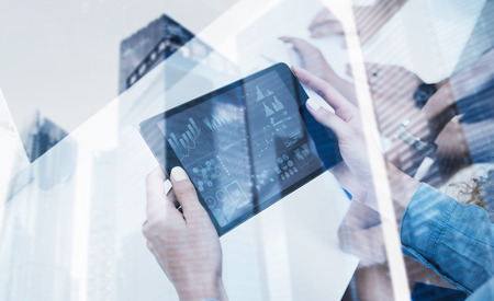 Closeup of female hands holding modern electronic tablet.Concept business people using mobile gadgets.Icon and diagramm on the display.Double exposure,skyscraper office building blurred background
