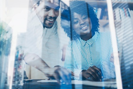 Concept of double exposure.Two young coworkers working together in a modern office.Black business partners discussing new startup project.Skyscraper office building blurred on background.Horizontal Stock Photo