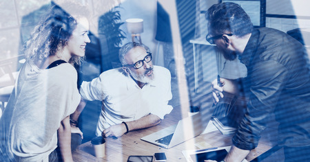 Concept of double exposure.Young team of coworkers making great work discussion in modern office.Bearded man talking with adult businessman.Skyscraper office building blurred on background.Horizontal