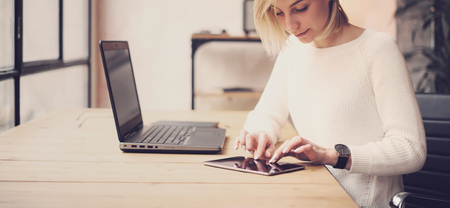 work table: Closeup view of young beautiful woman working at the wooden table.Female hand touching tablet on workplace.Concept business people using mobile devices.Horizontal wide, blurred background.
