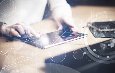 Online Business: Concept of virtual interfaces,digital icons,online connections.Closeup view  female finger touching black screen  tablet under the wooden table.Young business people using mobile devices. Stock Photo