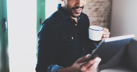 informal clothing: Closeup of young bearded African man using tablet while holding white cup in hand at modern coworking office.Concept people working with mobile gadget.Blurred brick wall on the background.Wide. Stock Photo