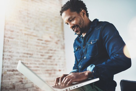 Bearded young African man smiling and using laptop while sitting at his modern coworking place.Concept of happy business people.Blurred background, flare effect. Stock Photo