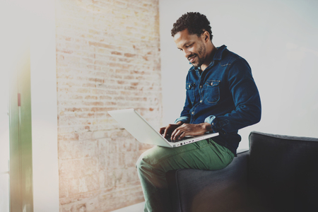 Smiling young African man working with laptop while sitting on sofa at his modern coworking place.Concept of happy business people.Blurred background, flare effect. Banque d'images