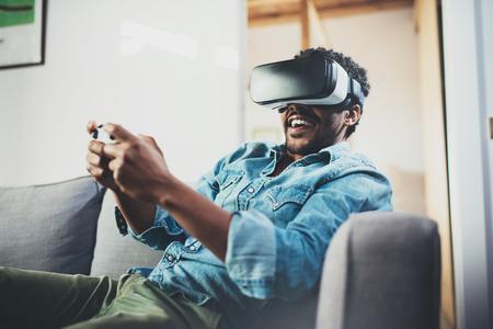 Uśmiechnięty afrykański mężczyzna cieszy się rzeczywistość wirtualna szkła podczas gdy siedzący na kanapie Szczęśliwy młody facet z vr słuchawki, 3d widowiskami lub kontrolera gamepad bawić się wideo grę w domu zamazany.