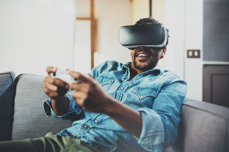 Bearded african man enjoying virtual reality glasses while sitting on sofa.Happy young guy with vr headset or 3d spectacles and controller gamepad playing video game at home.Blurred.