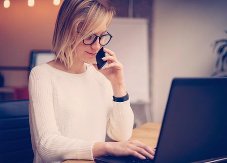 hermosa mujer joven que trabaja en la computadora portátil y hacer llamadas usando moderna workplace.Horizontal teléfono inteligente, fondo borroso, filtro de color.