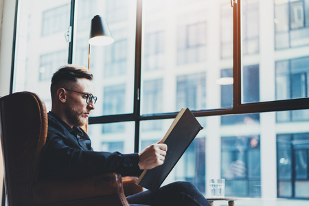 work book: Intelligent stylish businessman reading black book while sitting in vintage chair at his modern office.Young man relaxing after work day.Panoramic windows on blurred background.Horizontal,film effect. Stock Photo