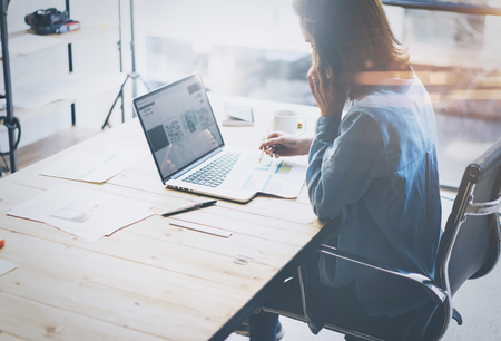 Account manager working process.Young business woman work with new startup project in office.Analyze document, plans.Modern laptop on wood table, papers, documents.Horizontal, blurred, flare.