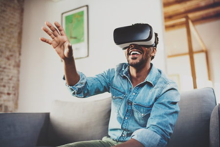 Concept of technology,gaming,entertainment and people.Happy bearded african man enjoying virtual reality glasses while relaxing on sofa at home.Blurred background. Фото со стока