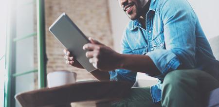 Homme africain souriant barbu avec tablette pour la conversation vidéo tout en vous relaxant sur le canapé dans le bureau moderne. Concept de jeunes gens d'affaires travaillant à la maison. Arrière-plan flou. Horizontal large. Banque d'images - 71533349