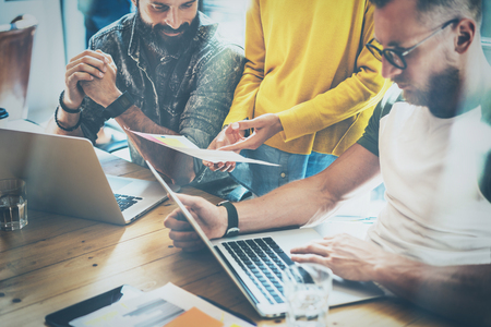 Group of three coworkers making great brainstorming during work process in modern office.Young bearded man watching document and smiling.Business people meeting concept.Horizontal, blurred.