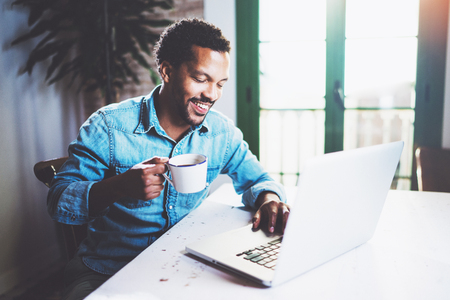 Happy bearded African man working at home while sitting the wooden table.Using modern laptop for new job search.Concept of young people work mobile devices.Blurred background. Stock Photo