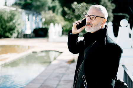 Portrait of pensive gray-haired adult businessman talking on smartphone while spending time in city park at sunny day.Horizontal,blurred background.