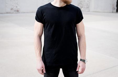 若い筋肉を生やした黒の t シャツとジーンズで、近代的な都市の中心のポーズを身に着けています。背景に空のコンクリート壁。Hotizontal のモックア
