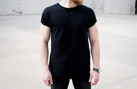 Young muscular bearded man wearing black tshirt and jeans posing in center of modern city. Empty concrete wall on the background. Hotizontal mockup, front view