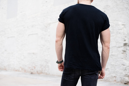 Young muscular bearded man wearing black tshirt and jeans posing in center of modern city. Empty concrete wall on the background. Hotizontal mockup, back view