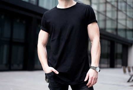 Young muscular man wearing black tshirt and jeans posing in center of modern city. Blurred background. Hotizontal mockup.