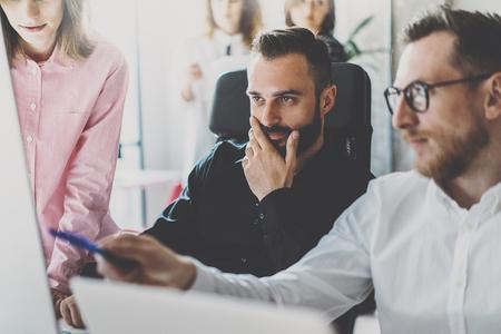 팀웍 개념입니다. 젊은 동료 현대 office.Group에 새로운 비즈니스 프로젝트를 논의합니다. 그룹의 세 사람의 데스크톱 컴퓨터에 보고서를 분석합니다. 가