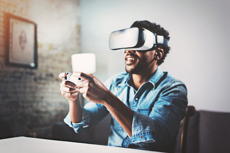 virtual reality simulator: Concept of technology,gaming,entertainment and people.African man enjoying virtual reality glasses while relaxing in living room.Happy young guy with VR headset playing video game at home.Blurred.