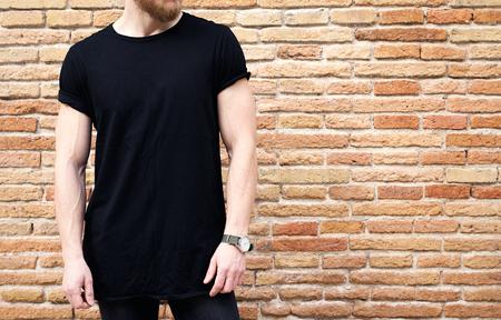 Opinión del primer del hombre musculoso barbudo que desgasta la camiseta y los pantalones vaqueros negros que presentan afuera. Pared de ladrillo marrón vacía del grunge en el fondo. Maqueta hotizontal. Foto de archivo - 72489069