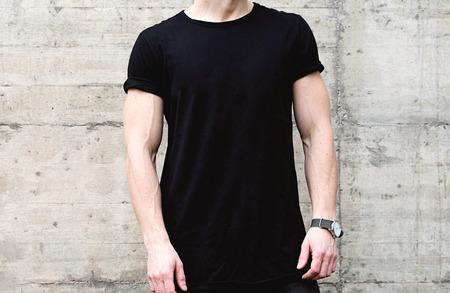 검은 tshirt와 청바지 현대 도시의 센터에서 포즈를 입고 젊은 근육 질의 남자의 근접 촬영보기. 배경에 빈 콘크리트 벽입니다. 수평으로 만든 모형.