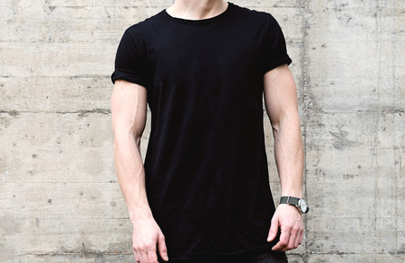 Closeup view of young muscular man wearing black tshirt and jeans posing in center of modern city. Empty concrete wall on the background. Hotizontal mockup.