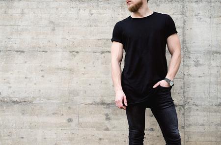 Joven musculoso hombre barbudo vistiendo camiseta negra y pantalones vaqueros posando en el centro de la ciudad moderna. Pared de concreto vacía en el fondo. Maqueta hotizontal.