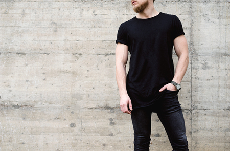 Young muscular bearded man wearing black tshirt and jeans posing in center of modern city. Empty concrete wall on the background. Hotizontal mockup. Stok Fotoğraf