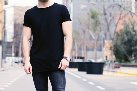 Closeup view of young muscular man wearing black tshirt and jeans posing on the street of the modern city. Blurred background. Hotizontal mockup.