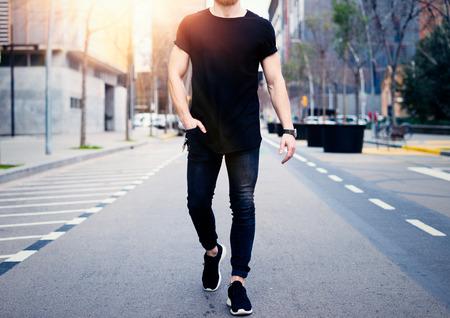 Giovane uomo muscoloso che indossa maglietta nera e jeans che camminano per le strade della città moderna. Sfondo sfocato. Mockup a livello orizzontale.