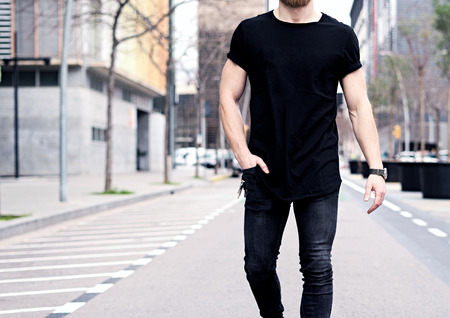 Closeup view of young muscular man wearing black tshirt and jeans walking on the streets of the modern city. Blurred background. Hotizontal mockup. 스톡 콘텐츠