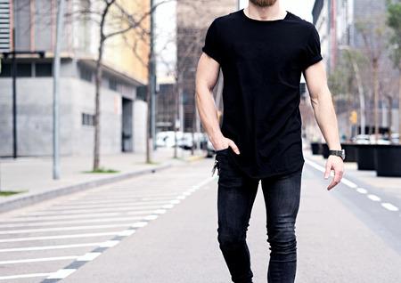 Gros plan de jeune vue homme musclé portant t-shirt noir et des jeans marchant dans les rues de la ville moderne. Arrière-plan flou. mockup Hotizontal. Banque d'images