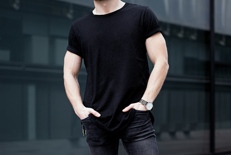 Young caucasian muscular man wearing black tshirt and jeans posing in center of modern city. Blurred background. Hotizontal mockup. Stockfoto