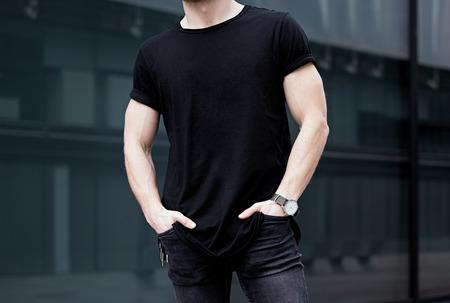 Junge kaukasischen muskulösen Mann mit schwarzen T-Shirt und Jeans posiert im Zentrum der modernen Stadt. Unscharfer Hintergrund. Hotizontal Mockup.