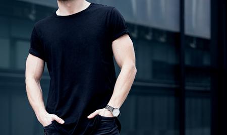 Closeup de joven caucásica muscular hombre llevaba camiseta negra y pantalones vaqueros posando en el centro de la ciudad moderna. Fondo borroso. Maqueta hotizontal.