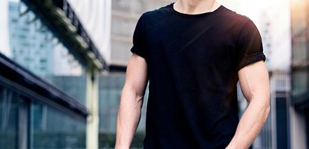 검은 색 tshirt와 청바지 현대 도시의 거리에 포즈를 입고 젊은 백인 근육 질의 남자. 흐리게 배경입니다. 수평 넓은 와이드 모델.