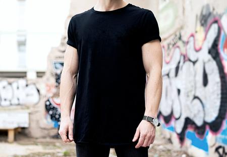 Jóvenes caucásicos muscular hombre vistiendo negro camiseta y pantalones vaqueros posando en el distrito moderno. Graffiti borrosa en el fondo. Maqueta hotizontal.